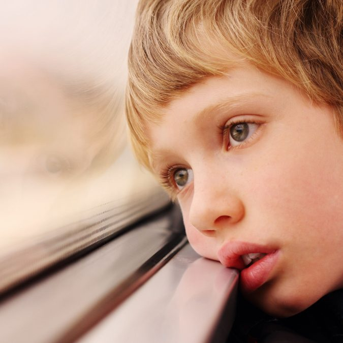 Young Boy with Head On Window Looking Outside