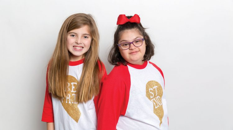 Two Young Girls Posing for Picture on White Background