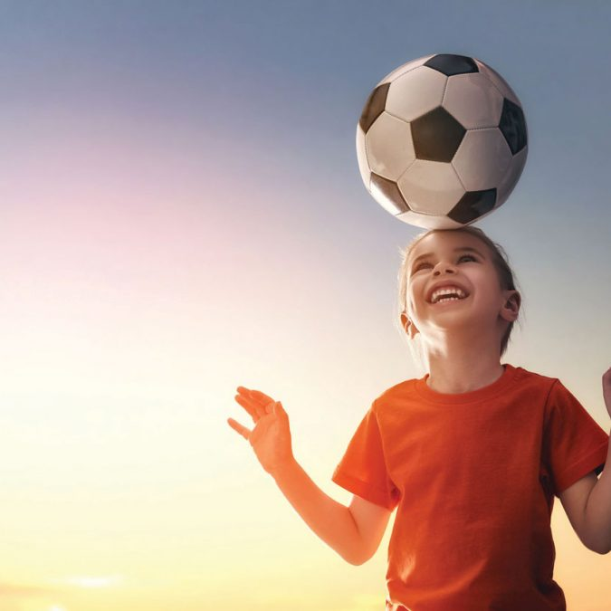 Young Girl with Soccer Ball on Her Head