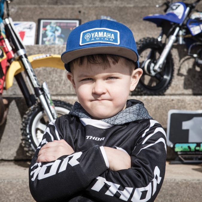Young Boy with Arms Folded Standing In Front of Dirt Bikes