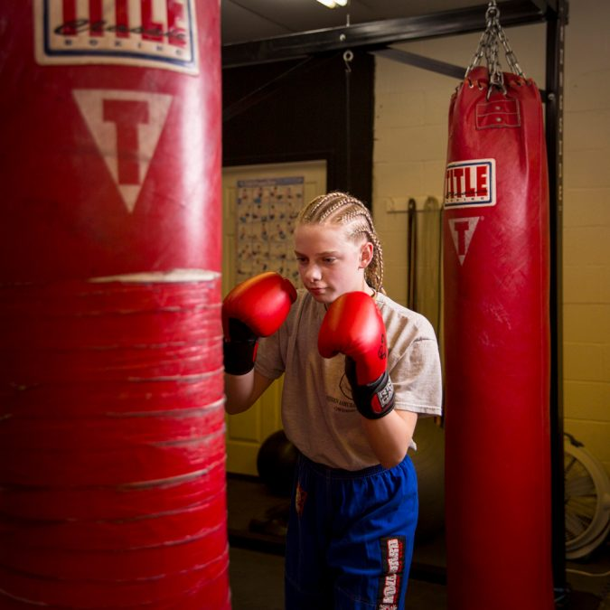 Girl with Punching Gloves Hitting a Punching Bag