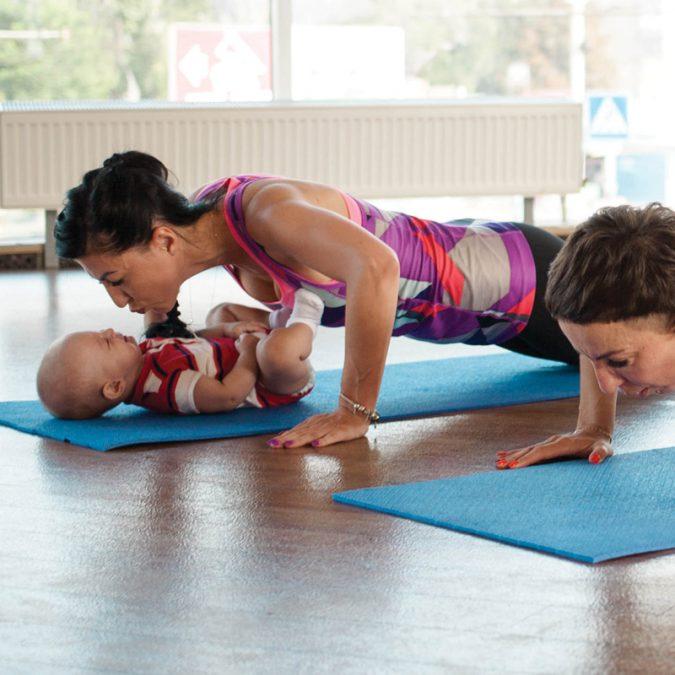 Women doing yoga with baby on yoga mat