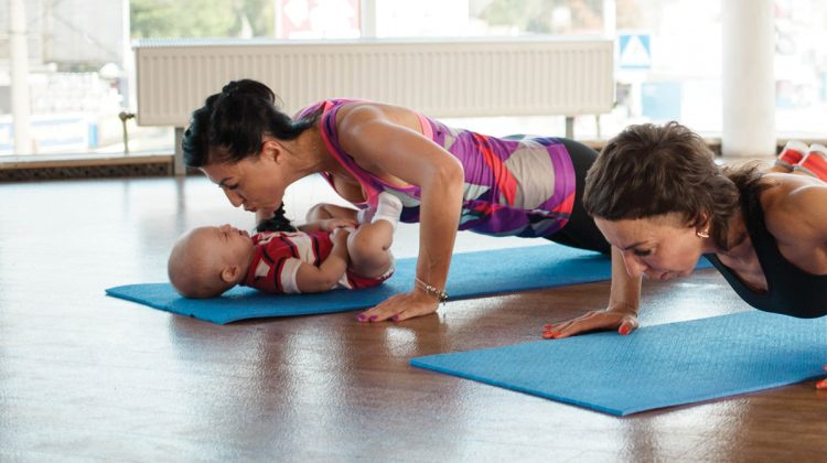 Women doing yoga with baby on yoga mat