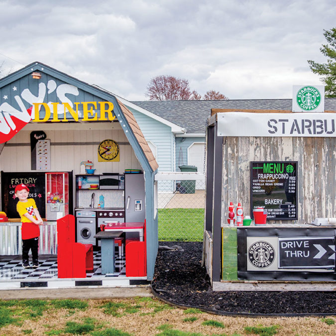 Four-year-old Tennyson Elder, posing in front of his diner and Starbucks playhouses.