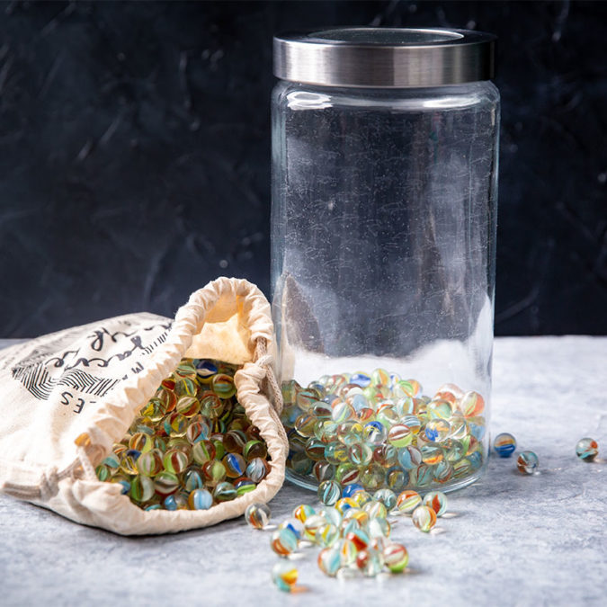 Glass jar and cloth bag filled with marbles