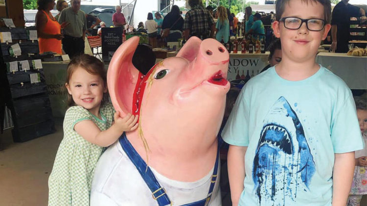 Kids pose next to a pig statue