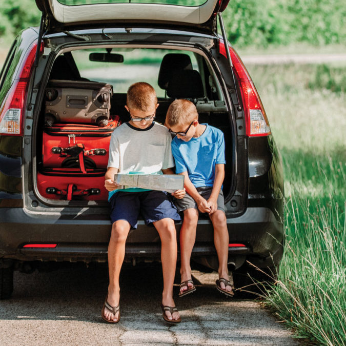 Boys looking at a map in the back of a car