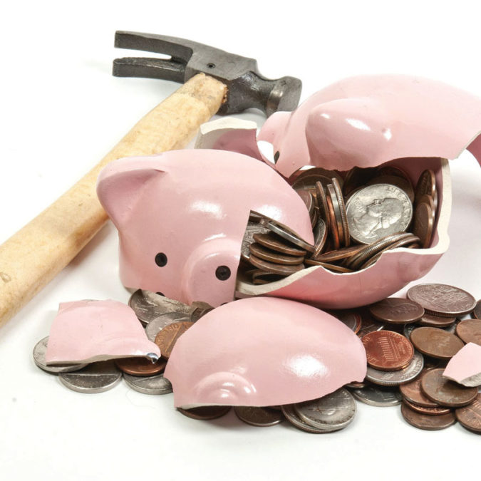 Broken piggy bank and hammer laying on white background