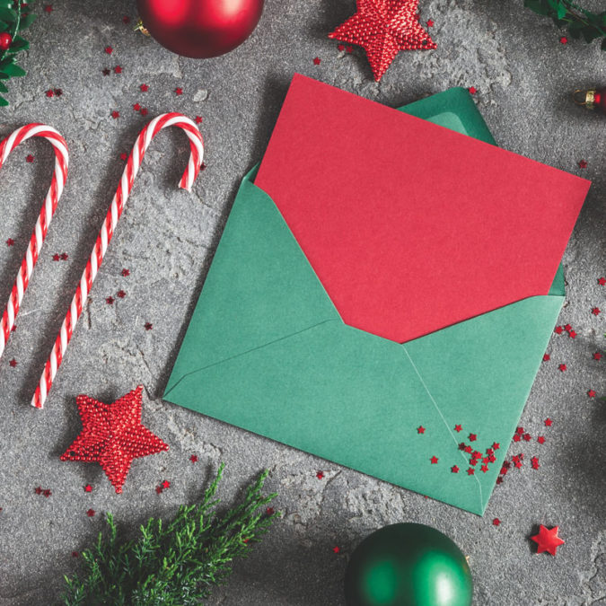 Overhead photo of red and green Christmas card in envelope, fake candy canes, presents and ornaments