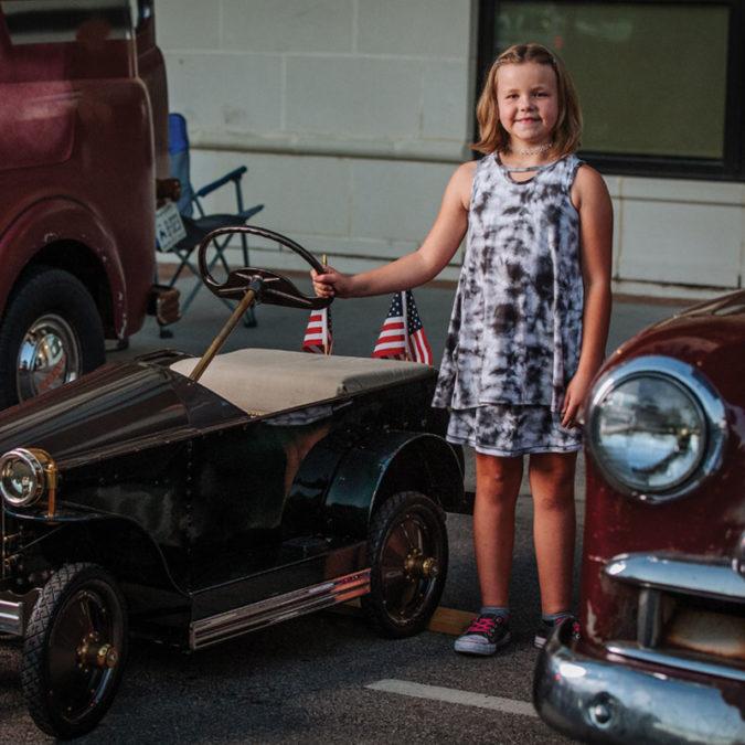 Bella Braden standing beside her restored car at a car show