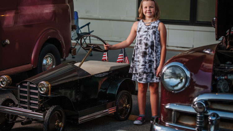 Bella Braden standing beside her restored car at a car show