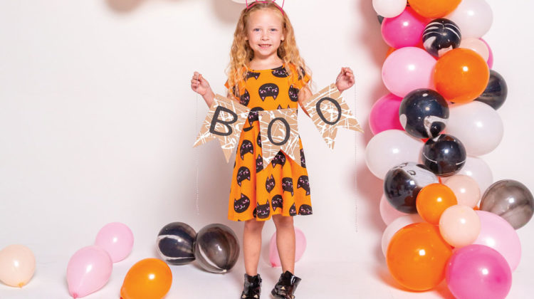 """Little girl in cat ears holding """"Boo"""" sign"""