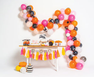Halloween decoration on white background, including balloons, streamers, cake, and other snacks