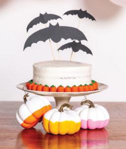 Halloween cake with paper bats on top and pumpkins below