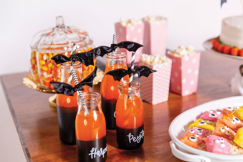 orange soda in customized glass bottles with fun straws and ribbons that look like bats