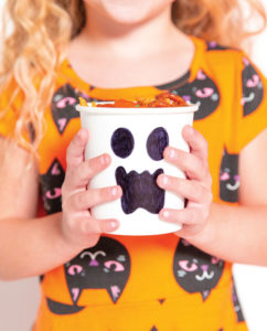 Little girl holding white cup with ghost face painted on with permanent marker