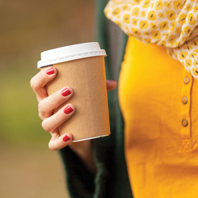 Woman holding coffee cup in autumn