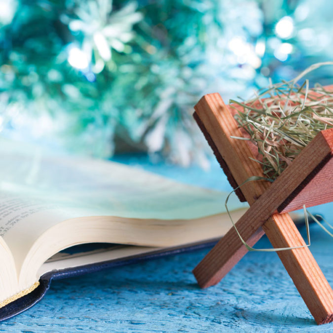 Tiny wooden manger beside Bible sitting on table