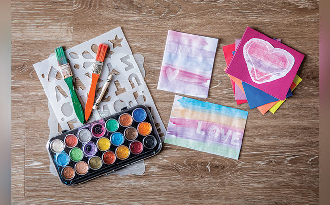 Watercolor supplies on a wooden floor