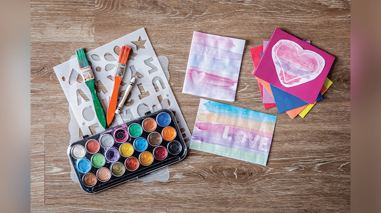 Watercolor supplies on a wooden floor